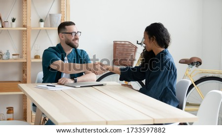 Happy businessman shaking hands with diverse woman job seeker. Smiling successful manager making deal with african american partner near laptop. Professional employee congratulations applicant.