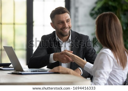 Happy businessman shaking hands with woman job seeker near laptop. Smiling successful manager making deal with female partner using pc. Professional employee congratulations applicant.