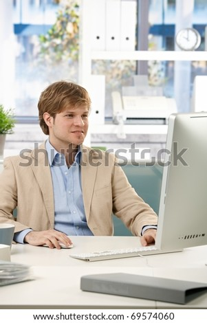 Happy businessman sitting at desk in office working with computer, looking at screen.?