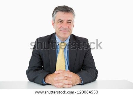 Happy businessman sitting at his desk on white background - stock photo