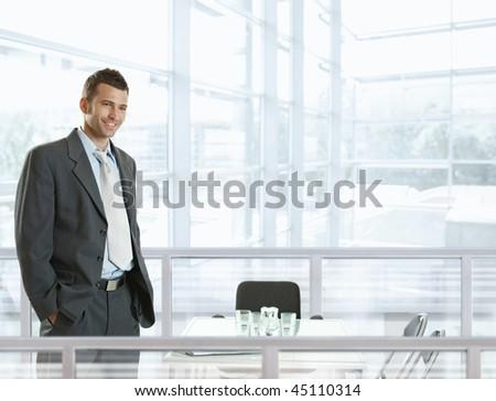Happy businessman standing behind office desk, smiling.