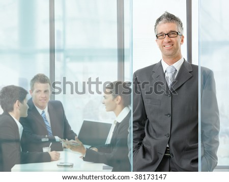Happy businessman standing in modern glass office, businesspeople having a meeting in the background.