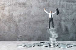 Happy businessman standing on silver coins on concrete wall background. Finance and success concept.