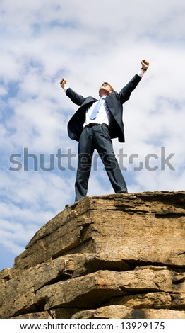 Happy businessman standing on the top of mount with his arms raised to the sky