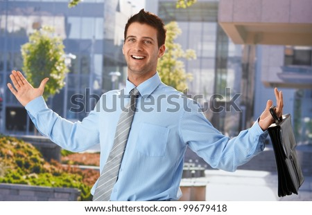 Happy businessman standing outside office, leaving from work, arms wide open, holding briefcase, smiling.