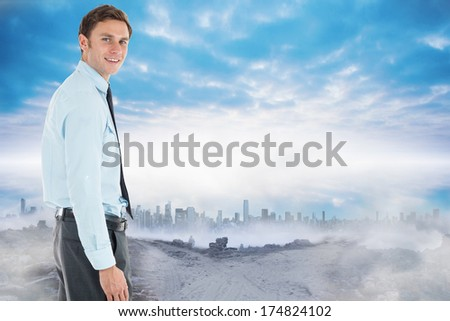 Happy businessman standing with hand in pocket against dusty path leading to city under the clouds