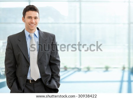 Happy businessman standing with hands in pocket in front of windows, looking at camera, smiling.
