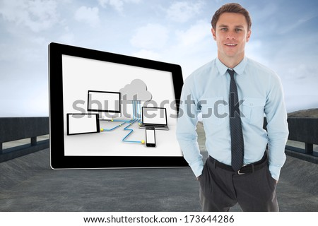 Happy businessman standing with hands in pockets against road leading out to the horizon