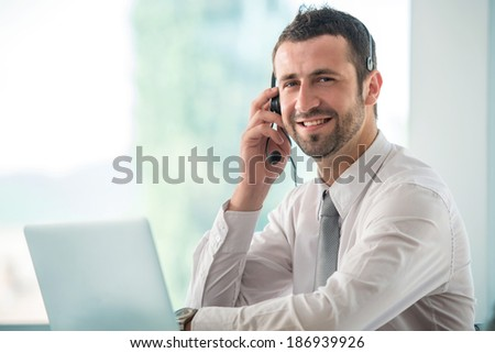 Happy businessman talking on headset in office