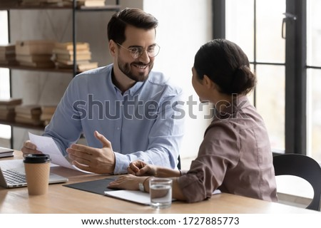 Happy businessman talking with indian businesswoman about successful finance report looking at worker. Diverse smiling woman and male manager discuss and looking decision in negotiation.