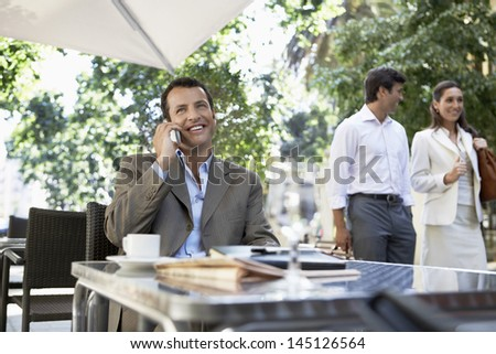 Happy businessman using cellphone at outdoor cafe with people in background