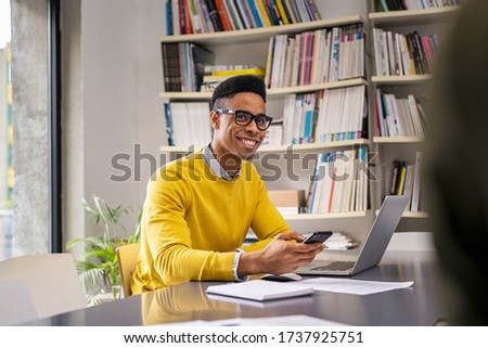 Happy businessman using computer at modern office while talking with a colleague. Smiling young man using smart phone for work. Creative guy using cellphone while working for a startup company.