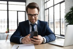 Happy businessman using online app on smartphone at office workplace. Employee wearing suit and glasses, texting and chatting on mobile phone, using cell for video call, shopping, quick payment