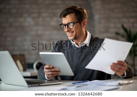 Happy businessman using touchpad and laptop while working on business reports in the office.
