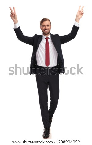 happy businessman walking and celebrating with hands in the air while making peace sign, full length picture