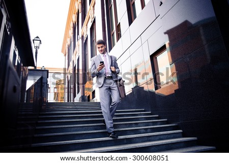 Happy businessman walking on the stairs and using smartphone outdoors stock photo