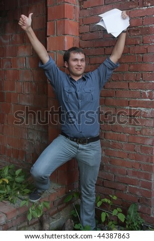 Happy businessman with documents against  the brick wall