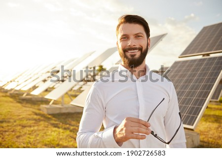 Happy businessman with glasses smiling and looking at camera while standing against photovoltaic panels on solar power station Stock photo ©