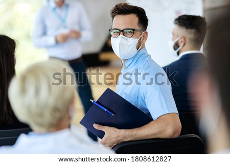 Happy businessman with protective face mask attending an educational event and looking at camera.