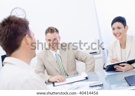 Happy businesspeople conducting job interview in brightly lit office, smiling.