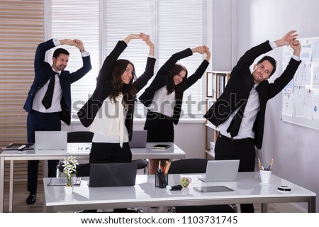 Happy Businesspeople Doing Stretching Exercise Behind Desk At Workplace