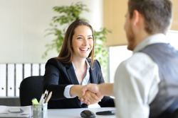 Happy businesspeople handshaking after deal or interview at office