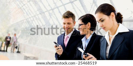 Happy businesspeople using mobile phones at office lobby - plenty of copyspace.
