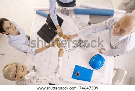 Happy businessteam celebrating success, smiling, clinking champagne glasses at office table, overhead view.?