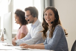 Happy businesswoman call center agent looking at camera posing at workplace, smiling female telemarketer operator in wireless headset working with computer in customer service support office portrait