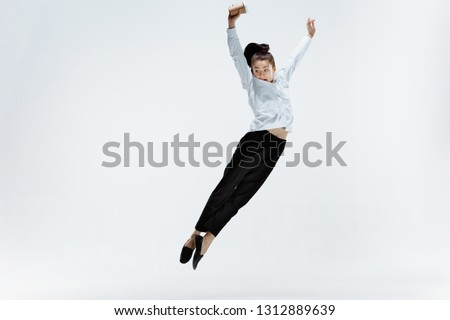 Happy businesswoman dancing and smiling in motion isolated on white studio background. Flexibility and grace in business. Human emotions concept. Office, success, professional, happiness, expression #1312889639
