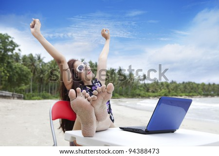 Happy businesswoman enjoying beautiful beach with laptop