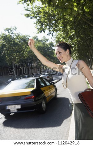 Happy businesswoman hailing a cab while standing at corner of the road