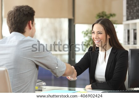Happy businesswoman handshaking with client closing deal in an office interior with a window in the background #406902424