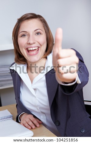 Happy businesswoman holding thumbs up at her desk in the office