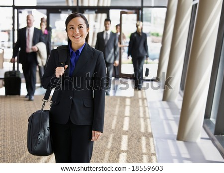 Happy businesswoman in full suit holding briefcase