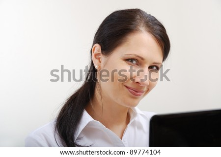 Happy businesswoman is working with a laptop. She is looking at the camera and smiling.