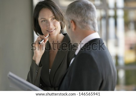 Happy businesswoman listening to male colleague in office