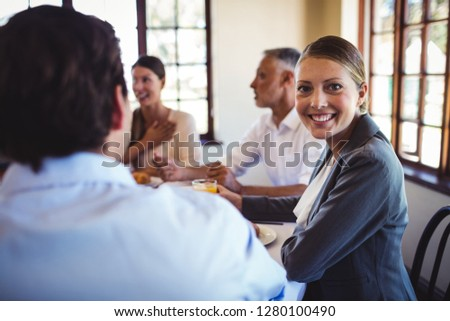 Happy businesswoman looking at camera in restaurant