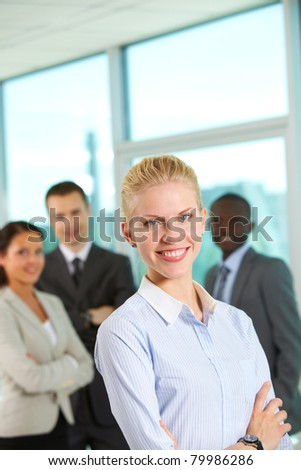 Happy businesswoman looking at camera on backround of three partners
