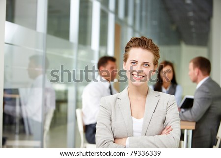 Happy businesswoman looking at camera on backround of working partners