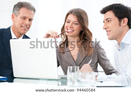 Happy businesswoman looking at coputer with her business colleagues at office