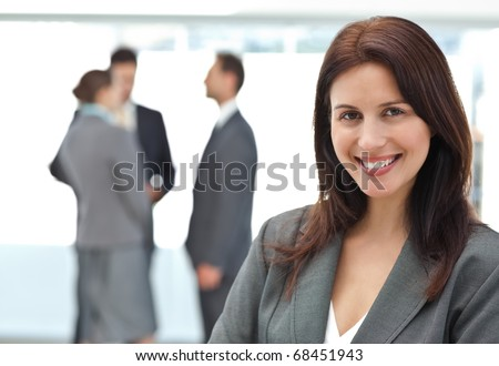 Happy businesswoman posing while her team discussing on the background