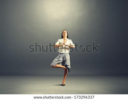 happy businesswoman practicing yoga over dark background