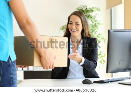 Happy businesswoman receiving a package sitting on a desk at office