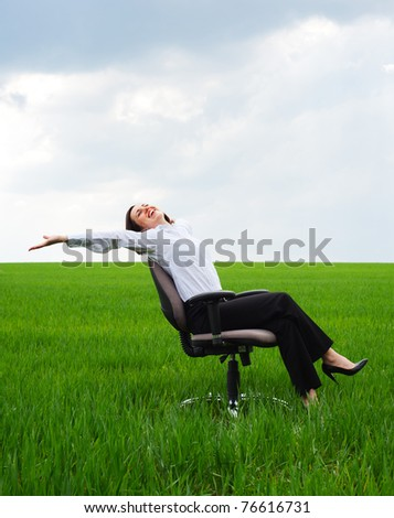 happy businesswoman resting on chair over green meadow