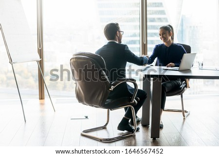 Happy businesswoman shaking hands with businessman job seeker in suit. Smiling successful manager making deal with partner near laptop. Professional employee holding cv and congratulations applicant.
