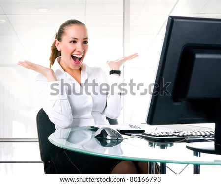 Happy businesswoman sits at the computer on the office