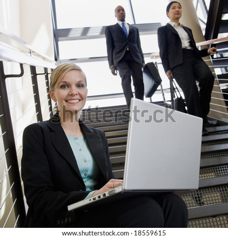 Happy businesswoman sitting and working on laptop on office stairs