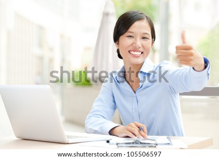 Happy businesswoman sitting at her workplace and showing thumbs up