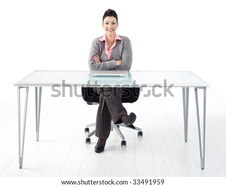 Happy businesswoman sitting at office desk, smiling. Full length portrait. Isolated on white background.